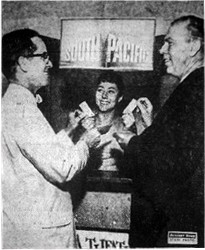 """LOOK WHO'S BUYING TICKETS! - Although they are donating the theater for 'South Pacific' premiere, John Denmen, left, city manager of Fox Wasatch Theaters, and Dick Frisbey, manager of the Villa Theater, purchase tickets for 'South Pacific' benefit premiere. Inez Hales is the cashier."""